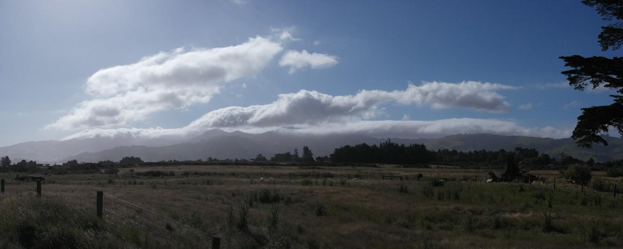 Coole Wolkenformationen wälzen sich über die an Dunedin angrenzenden Berge