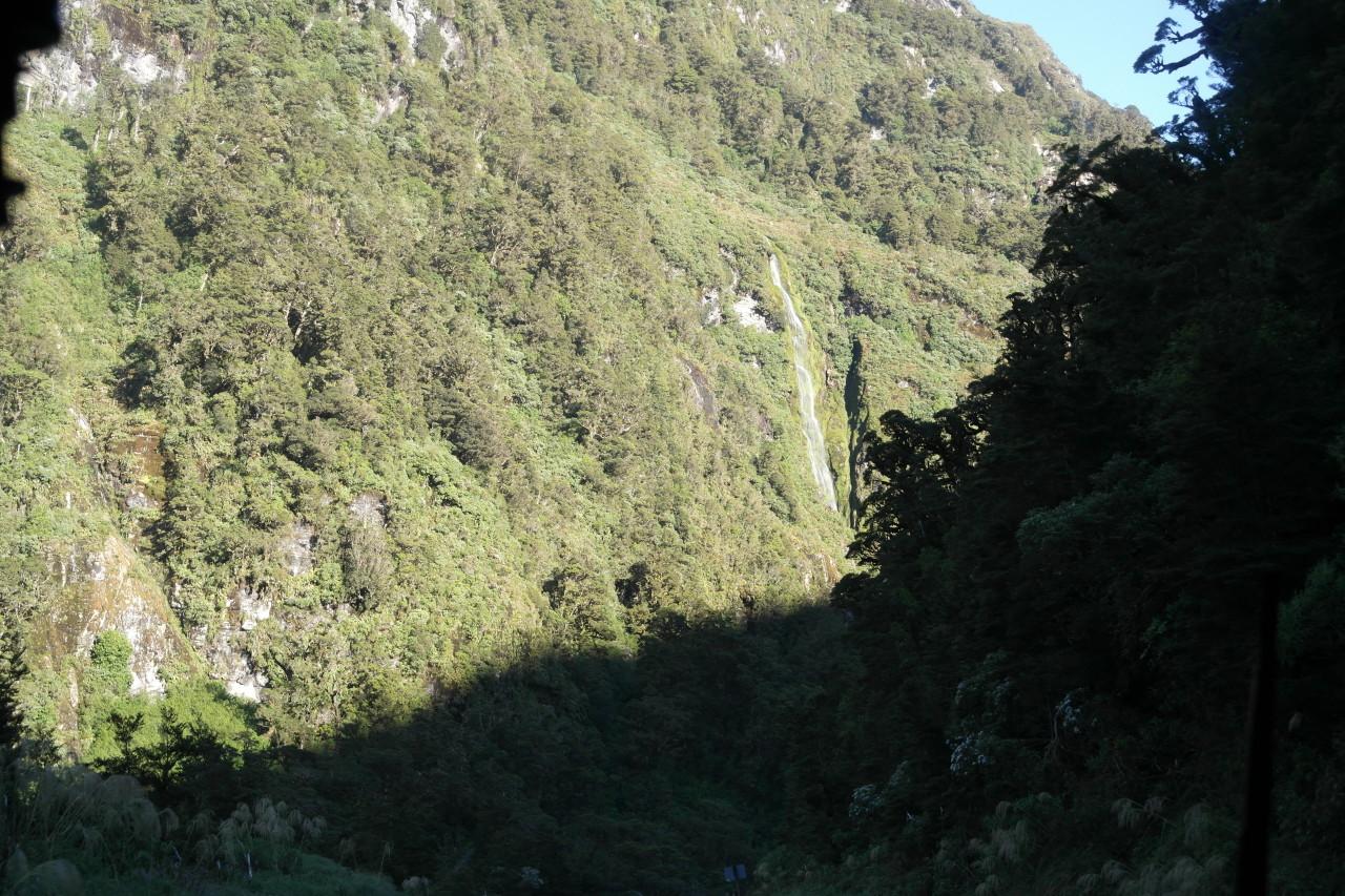 Die Passstraße ist eine Schotterstraße und schlängelt sich durch dichten Regenwald.