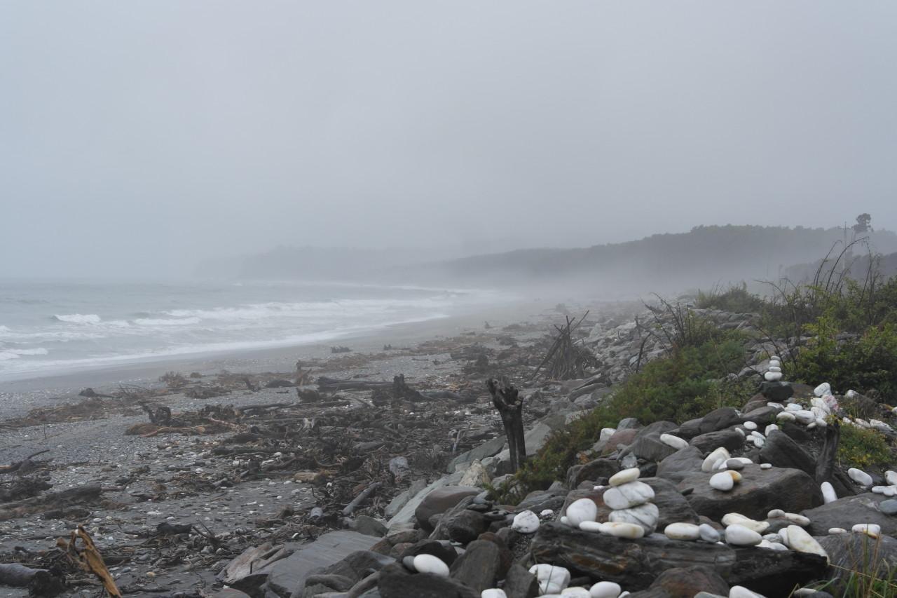 Sturm am Meer zwischen mit Glückwünschen beschrifteten Steinchen. Das Wetter heute war ein normaler Tag, es geht wohl noch viel schlimmer.